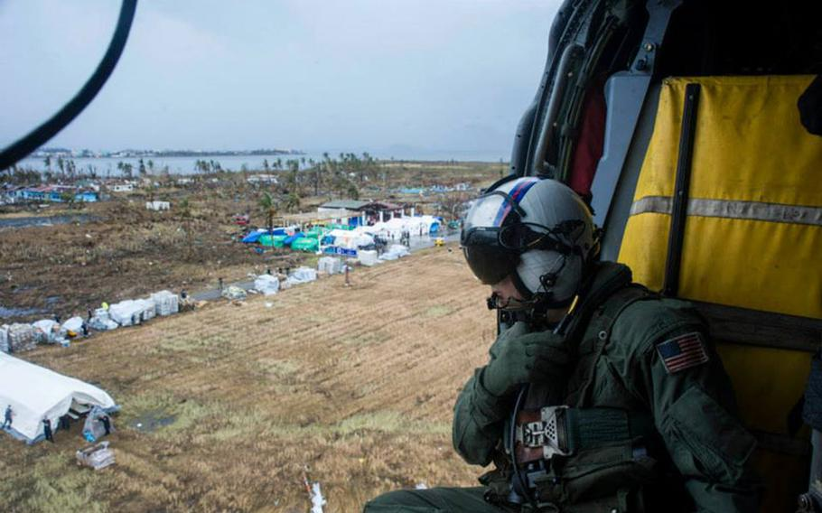 Petty Officer 2nd Class Justin Peach, from Riverside, Calif., prepares to drop supplies from an MH-60S Sea Hawk helicopter from the Golden Falcons of Helicopter Sea Combat Squadron 12, into Tacloban in support of Operation Damayan.