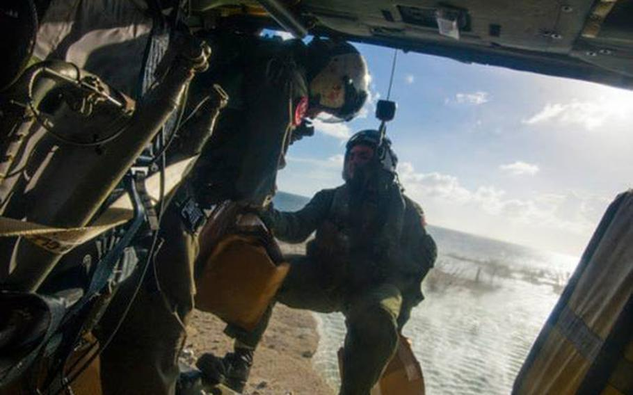 Petty Officer 2nd Class Justin Peach, right, from Riverside, Calif., prepares to drop supplies from an MH-60S Sea Hawk helicopter from the Golden Falcons of Helicopter Sea Combat Squadron 12, into Tacloban in support of Operation Damayan.