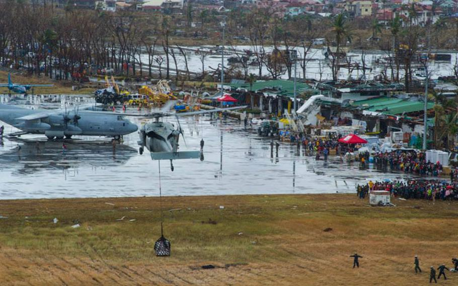 An MH-60S Sea Hawk helicopter from the Island Knights of Helicopter Sea Combat Squadron 25 drops supplies onto Tacloban Air Base in support of Operation Damayan.