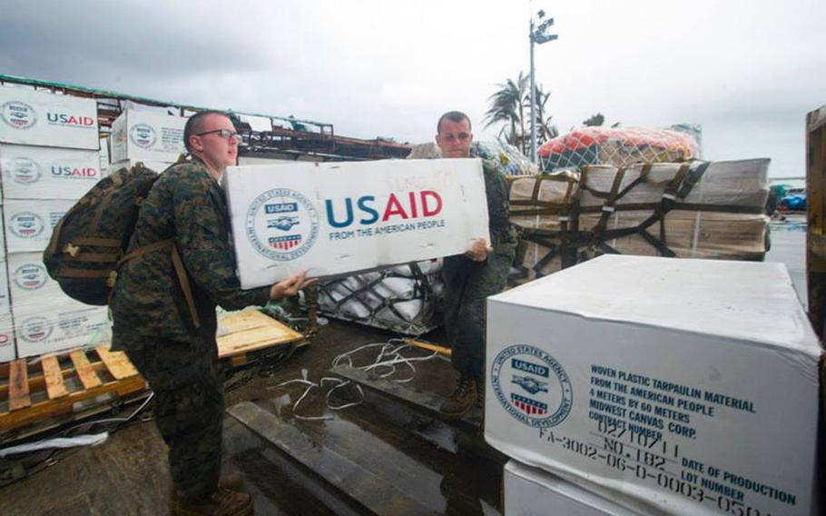 Petty Officer 3rd Class Eric Chiarito, left, from Hyde Park, N.Y., and Marine Sgt. Jonathan Thornton, from Lake Havasu, Ariz., load supplies onto a forklift at Tacloban Air Base in support of Operation Damayan.