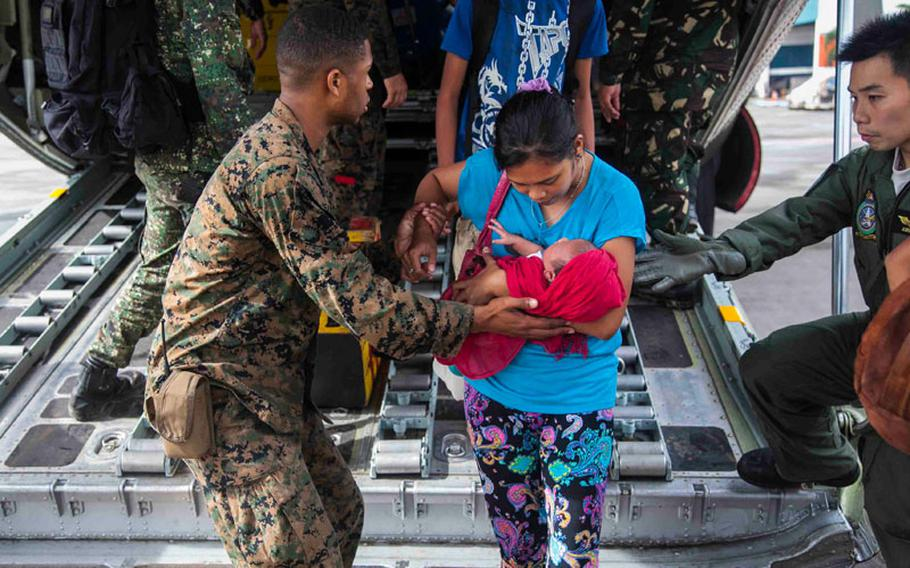 U.S. Marine Lance Cpl. Xavier L. Cannon and members of the Philippine Armed Forces help civilians displaced by Typhoon Haiyan disembark a C-130 aircraft Nov. 13 at Villamor Air Base as part of Operation Damayan.