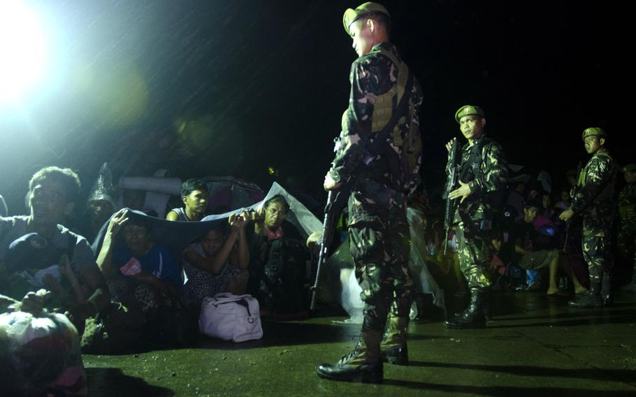 Philippine Army guards maintain order among typhoon victims waiting to board a flight out of Tacloban Airport bound for Villamor Airbase, Manila, Philippines, November 15, 2013.