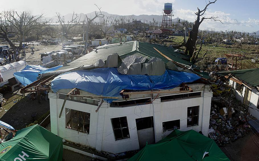 First responders set up a medical treatment area inside a storm-struck building just outside of Tacloban Airport, Tacloban, Philippines, to treat victims injured by Super Typhoon Haiyan.