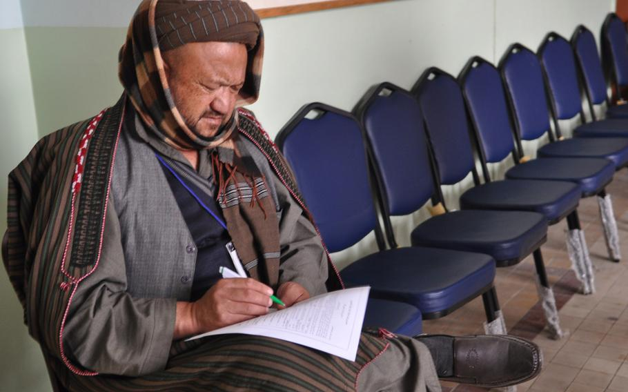 A member of the Afghan Loya Jirga reads through a proposed security agreement with the United States that would pave the way for international troops to stay in Afghanistan past the end of 2014. The jirga, a gathering of 2,500 community leaders from around the country, was convened by President Hamid Karzai who has said he will respect the council's decision on the security agreement.