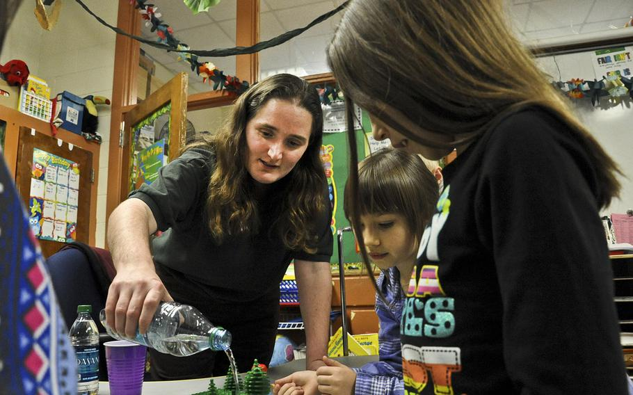 Magen McCollough, Williamsburg Environmental Group civil engineer, pours water over a simulated habitat to show the effects of water runoff during the Introduce a Girl to Engineering Day at John H. Russell Elementary School in Quantico, Va., in February 2012. The Pentagon has asked the RAND Corp. to study whether the DOD still needs to run schools in the United States.