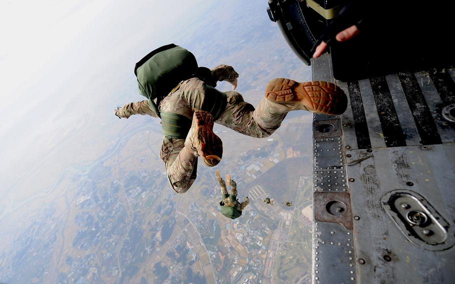 A pararescueman from the 31st Rescue Squadron freefalls with a parachute after jumping from a 33rd Rescue Squadron HH-60 Pave Hawk during training scenarios for PAIFIC THUNDER 2012 at Osan Air Base, South Korea, on Oct. 12, 2012.