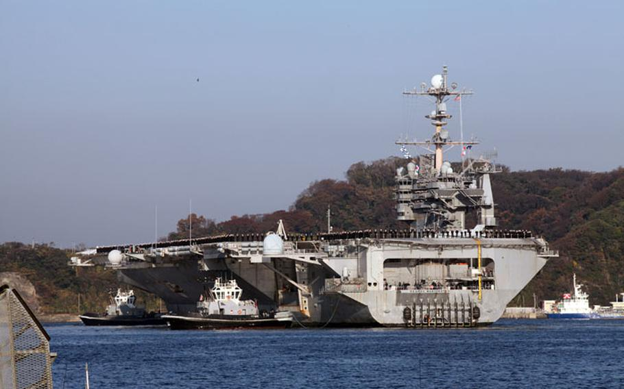 """USS George Washington sailors """"man the rails"""" as the carrier pulls in to port at Yokosuka Naval Base, Dec. 5. The sailors stood at parade-rest for more than an hour while their families stood by awaiting their return."""