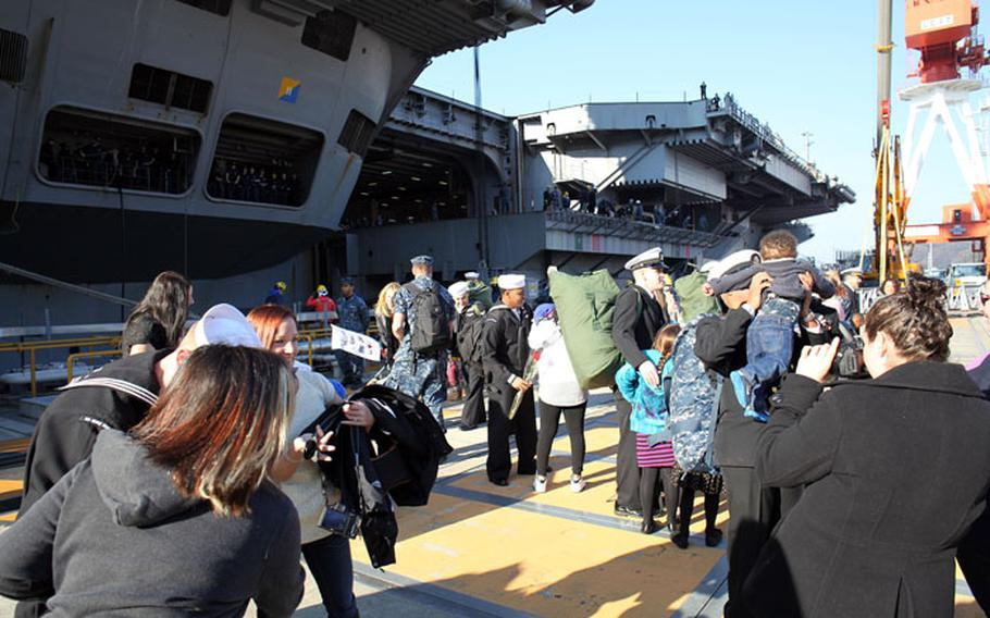 Sailors from the USS George Washington are greeted by their family members after the ship returned to port at Yokosuka Naval Base, Dec. 5. The carrier returned from the Phillipines where they assisted with typhoon aid.