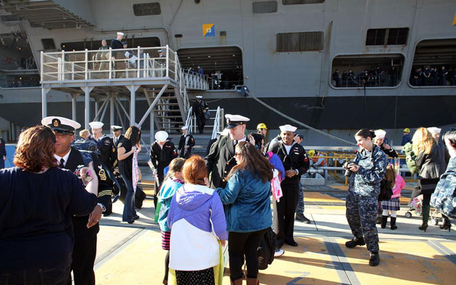 Family members greet USS George Washington sailors as they leave the ship Dec. 5. The carrier returned to port at Yokosuka Naval Base after completing their humanitarian mission in the Phillipines.