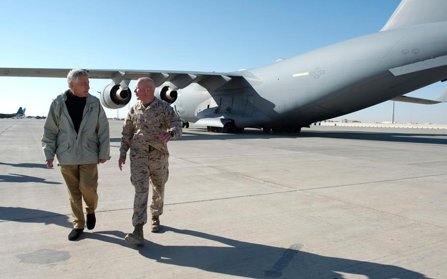U.S. Defense Secretary Chuck Hagel walks with Marine Corps Maj. Gen. Walter Miller Jr., commander of the ISAF's southwest region, at Camp Bastion in the Helmand province of Afghanistan, Dec. 8, 2013.