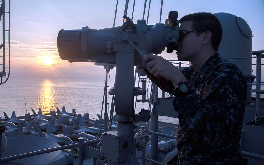 Petty Officer 2nd Class Jeremy Blaising uses ship-mounted binoculars to monitor navigation points as the aircraft carrier USS George Washington (CVN 73) arrives in Singapore for a scheduled port visit, on Oct. 26, 2013.