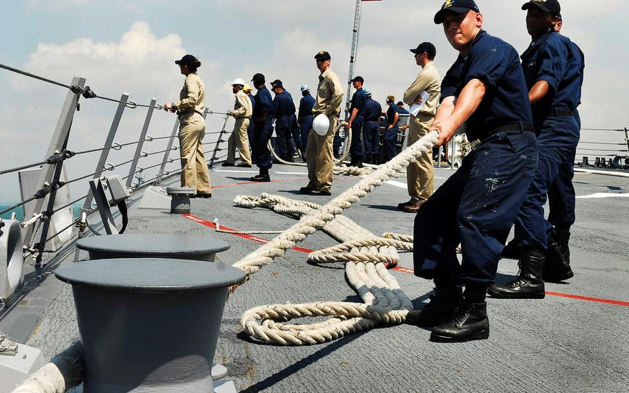 Sailors heave a mooring line on the forecastle aboard the Arleigh Burke-class guided-missile destroyer USS Kidd as the ship moors pier side at Changi Naval Base, Singapore, on April 4, 2009.