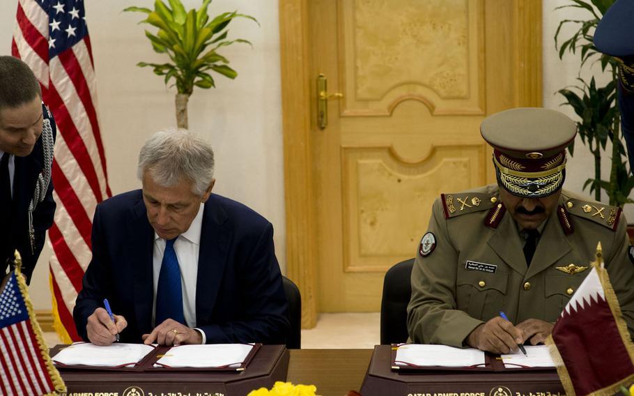 U.S. Defense Secretary Chuck Hagel, left, signs a renewal of a defense cooperation agreement with Maj. Gen. Hamad bin Ali al-Atiyah, the Qatari minister of state for defense affairs, in Doha, Qatar, Dec. 10, 2013.