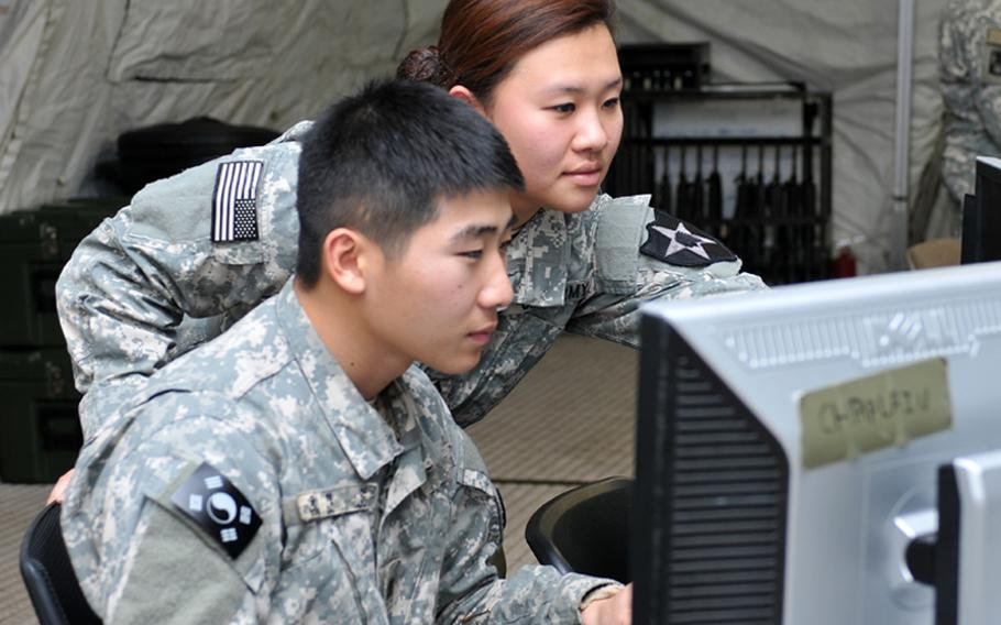 U.S. Army Pfc. Kayla Shin and KATUSA Cpl. Yoon Duk, both of the 2ID chaplain office, research information during the Warpath III exercise at Camp Mobile, South Korea, on Dec. 12, 2013.