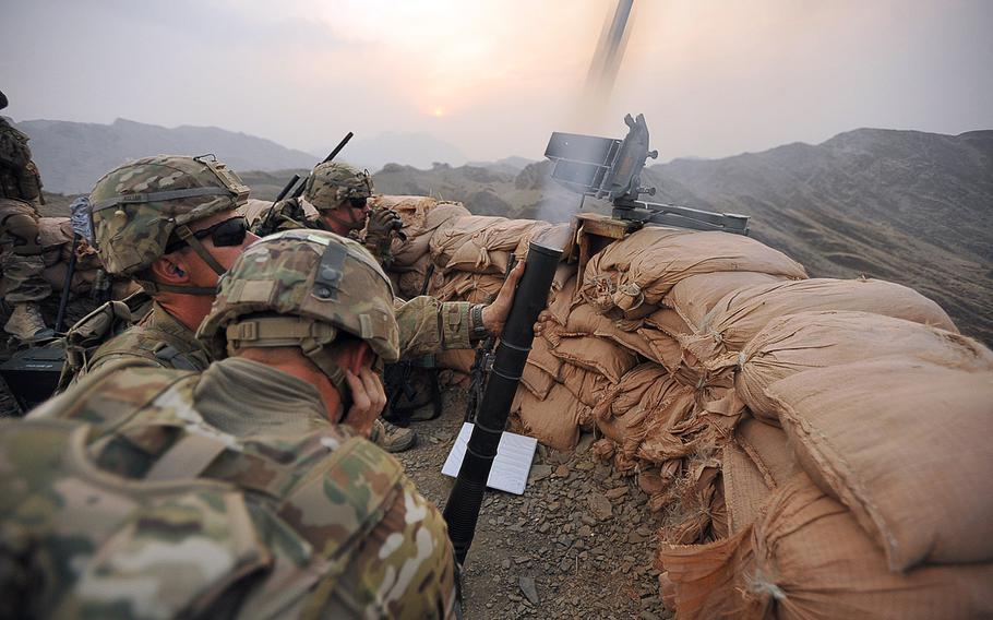 U.S. Army Spc. William Marsh covers his ears as Sgt. John Keller fires a shell from a M224 60mm mortar on Forward Operating Base Torkham, Afghanistan, on Sept. 27, 2013.
