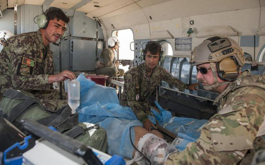 Medics with the Afghan air force work with the NATO Air Training Command-Afghanistan advisers to transport an injured soldier from a mission near Ghorak, Afghanistan, Sept. 23, 2013.