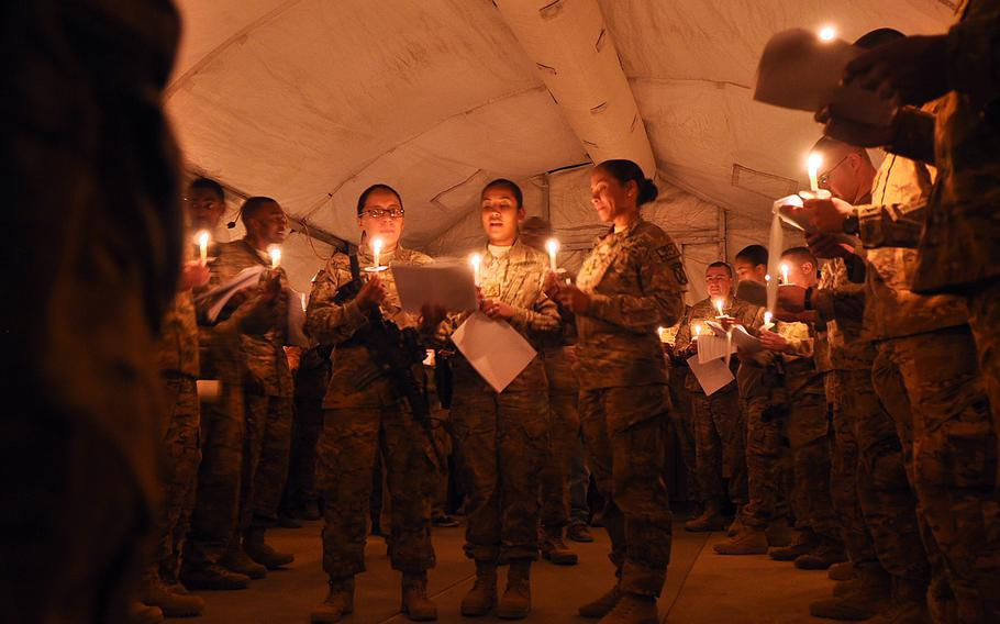 Servicemembers sing Silent Night during a candle-lit Christmas Eve service at Forward Operating Base Gamberi in Afghanistan.