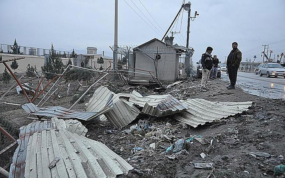 Police hovered around the site of the bombing in Kabul, in which three ISAF troops died and several Afghan civilians were wounded. The blast destroyed nearby fences and corrugated steel walls.
