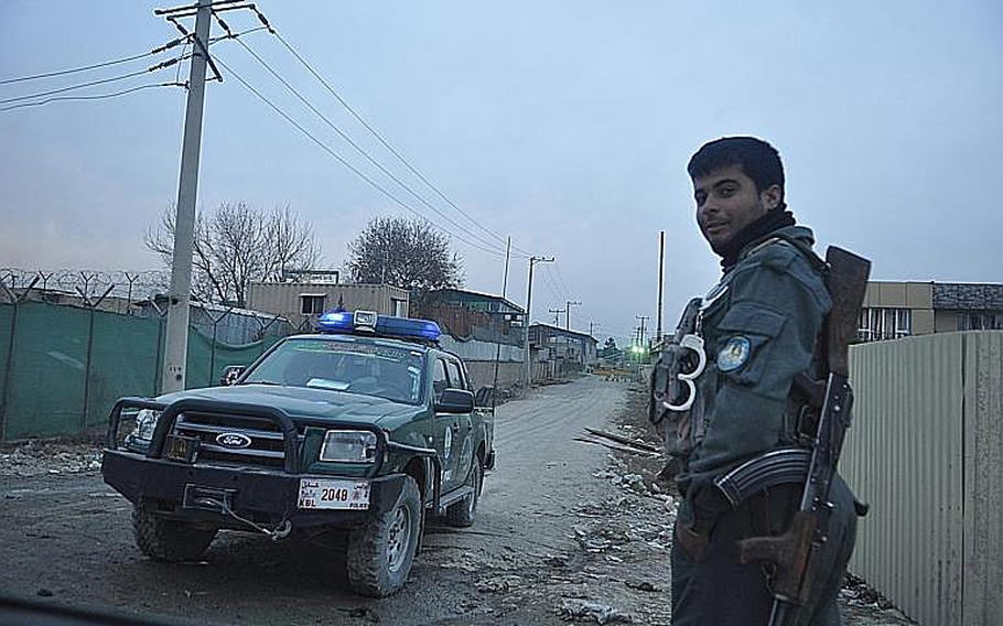 Police stand guard near the site in Kabul where a car bomb killed three ISAF troops and injured several Afghan civilians in December 2013. U.S. troops also stood watch outside of nearby Camp Phoenix.