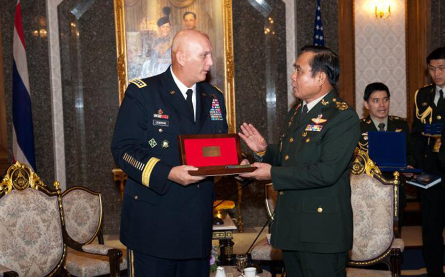 In this file photo from July 20, 2012, U.S. Army Chief of Staff Gen. Raymond T. Odierno, left, exchanges gifts with Thai Army Chief of Staff Gen. Prayuth Chan-ocha during Odierno's visit to Bangkok, Thailand.
