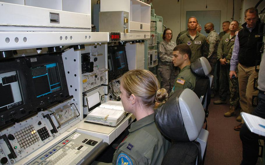Servicemembers sit inside a nuclear launch control simulator at F.E. Warren Air Force Base used to train missile officers. The simulator is a mockup of a real launch control center.