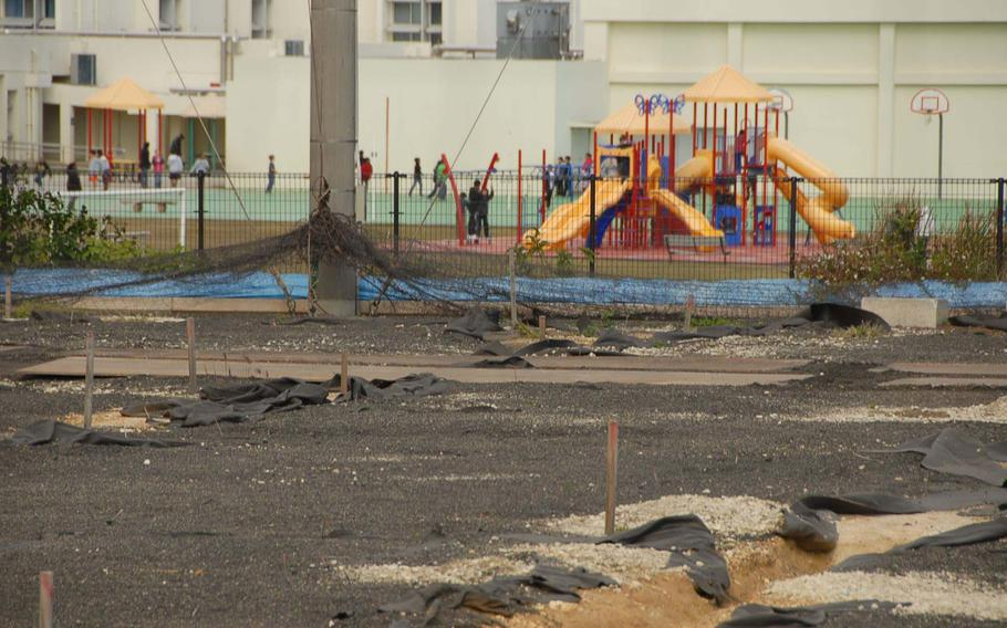 Survey stakes mark the Japanese soccer field where buried drums containing herbicide and dioxin residue were found while children play outside of nearby Amelia Earhart Intermediate School on Kadena Air Base, Okinawa.