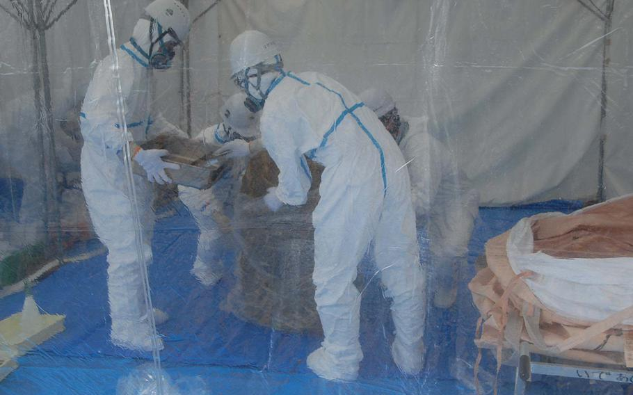 Inside a plastic-draped tent, Japan Ministry of Defense workers examine a badly rusted drum unearthed Jan. 28, 2014, from a soccer field near Kadena Air Base schools where 22 dioxin- and herbicide-laced barrels were found last year.