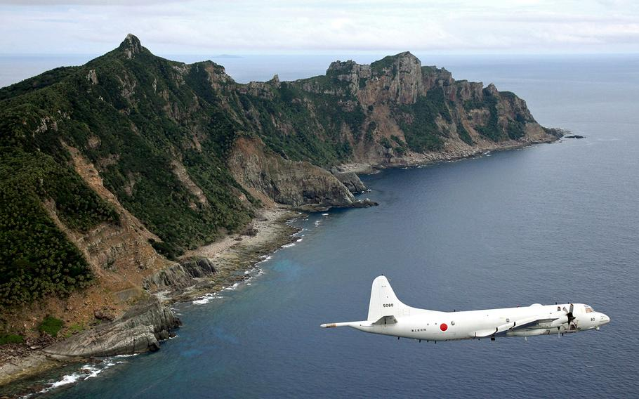 A Japan Maritime Self-Defense Force P-3C Orion surveillance plane flies over disputed islands in the East China Sea, called Senkaku in Japan and Diaoyu in China, in this Oct. 13, 2011, file photo.