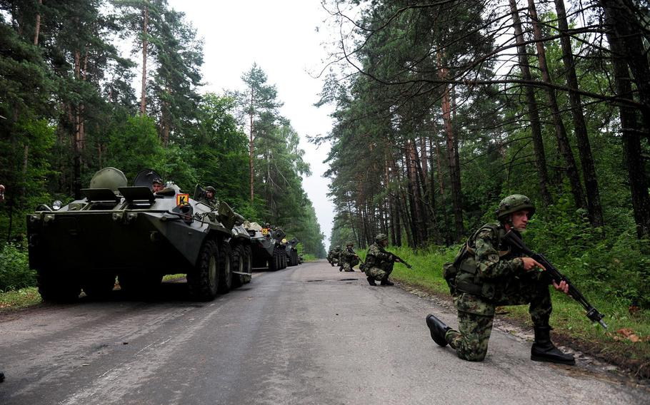 Serbian soldiers scan the forest for simulated enemy forces while providing security for their convoy during exercise Rapid Trident 2013 in Yavoriv, Ukraine, July 12, 2013. Planning for Rapid Trident 2014 -- a large, USAREUR-led multinational exercise scheduled for July -- is ongoing despite the crisis in Ukraine, according to a USAREUR spokesman.
