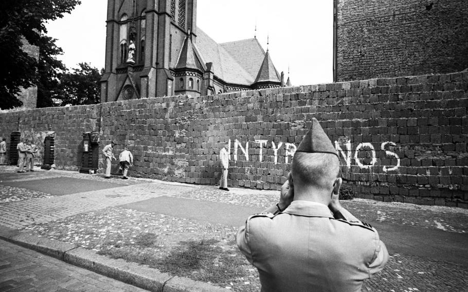 A West Point cadet poses for a photo in front of the Berlin Wall at the Church of Reconciliation in 1964.