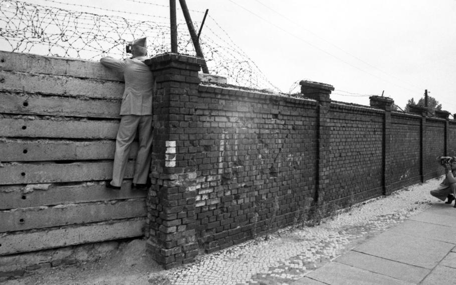 A West Point cadet takes a photo of a classmate sneaking a look over the Berlin Wall in 1964.
