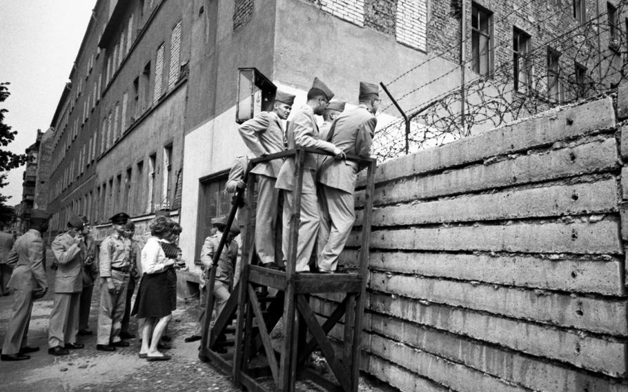 West Point cadets line up with other visitors take a look across the still-basic Berlin Wall in August, 1964.