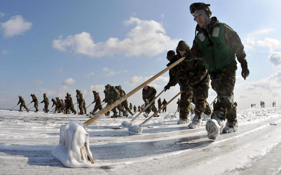 U.S. servicemembers aboard the USS Reagan scrub the external surfaces on the flight deck and island superstructure of the aircraft carrier to remove potential radiation contamination on March 23, 2011, while at sea off the coast of Japan where the ship was operating to provide humanitarian assistance in support of Operation Tomodachi.