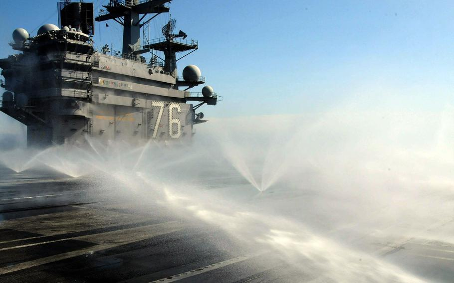 The USS Ronald Reagan conducts a countermeasure wash down to decontaminate the flight deck on March 23, 2011, while at sea off the coast of Japan where the aircraft carrier was operating to providing humanitarian assistance in support of Operation Tomodachi.