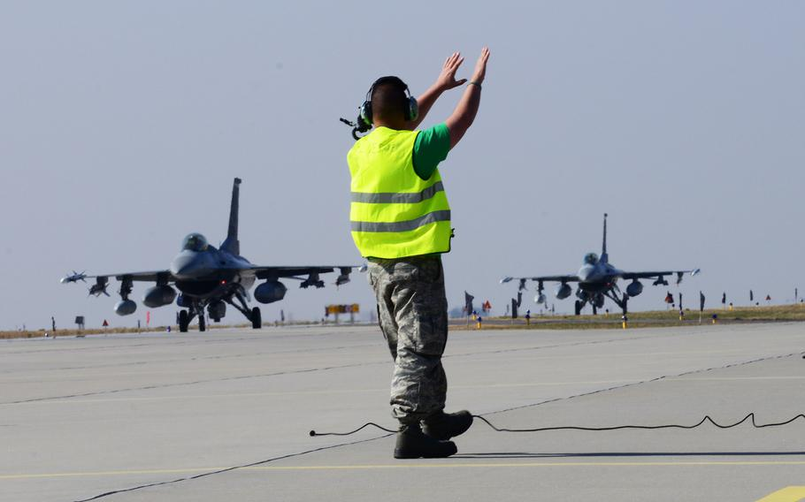 A crew chief guides 555th F-16 Fighting Falcons into place, March 14, 2014, at Lask Air Base, Poland. A total of twelve 555th Fighter Squadron F-16 Fighting Falcons and approximately 200 military personnel arrived in Poland in response to the Ukraine crisis.