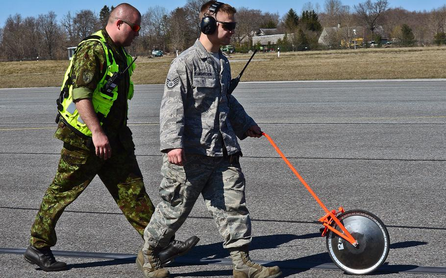 U.S. Air Force Staff Sgt. Josh Nicholson, 48th Air Expeditionary Group aircraft arresting systems craftsman and Estonian air force Master Sgt. Oleg Tsakuhhin, measure the pull out length of the purchase tape after a certification barrier engagement at Amari Air Base, Estonia, April 22, 2014.