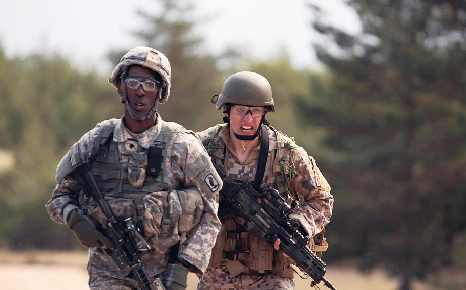 An American paratrooper from the 173rd Infantry Brigade Combat Team and a Latvian soldier sprint to the finish line Wednesday, April 30, 2014, during a stress shooting exercise that tested their endurance and marksmanship under rigorous physical conditions.