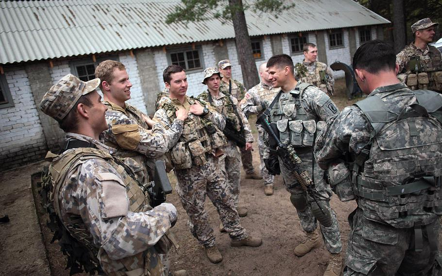 Latvian and American soldiers chat Wednesday, April 30, 2014, before being teamed up to run a stress shooting course that tested their endurance and marksmanship under rigorous physical conditions.