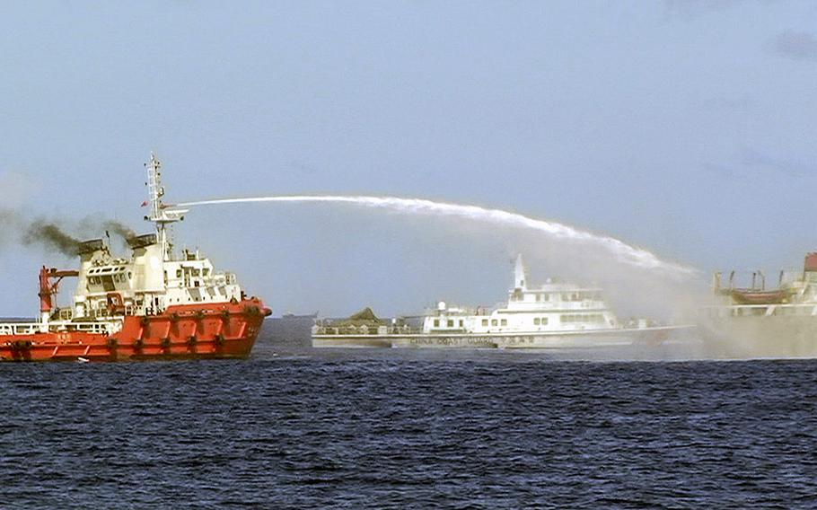 A Chinese ship, left, shoots a water cannon at a Vietnamese vessel, right, while a Chinese Coast Guard ship, center, sails alongside in the South China Sea, off Vietnam's coast, on Wednesday, May 7, 2014.