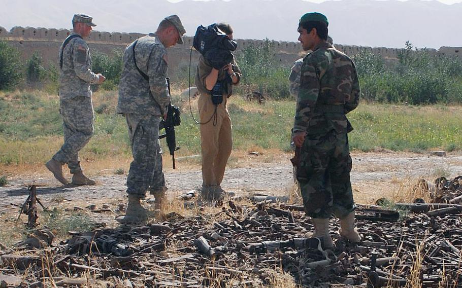 Personnel based at Forward Operating Base Mike Spann walk past rusted weapons on the grounds of the Kala-Jangi fortress, on Nov. 19, 2007, six years after the November 25, 2001, riot by Taliban prisoners, that resulted in the death of Mike Spann, the first American casualty of the war in Afghanistan.