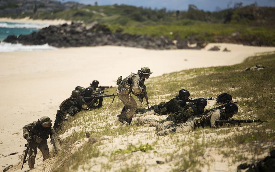 Two Japan Ground Self-Defense Force soldiers (left and center) advance to cover while their squads provide cover during an amphibious assault at Pyramid Rock Beach. The JGSDF conducted the training exercise with U.S. Marines with 3rd Reconnaissance Battalion, based in Okinawa, Japan.