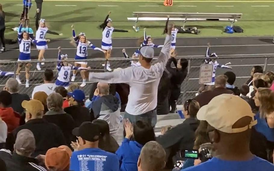 """Retired Air Force Major Rolland """"Hekili"""" Holland, known as """"Cheer Dad,"""" performs in sync with the cheerleaders from his daughter's high school in Yorktown, Va. in this screenshot taken from an Oct. 1, 2020 video posted to social media."""