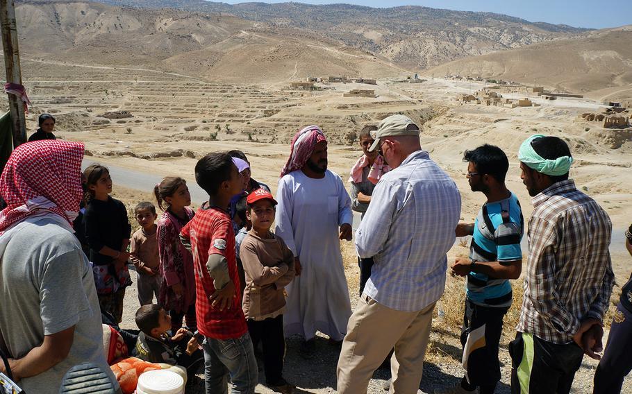 A member of the U.S. Mount Sinjar Assessment Team talks with locals near Sinjar, Iraq, on Aug. 13, 2014.