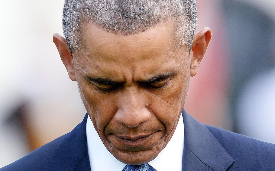 U.S. President Barack Obama observes a moment of silence to mark the 13th anniversary of the 9/11 attacks on Thursday, Sept. 11, 2014, on the South Lawn of the White House in Washington, D.C.