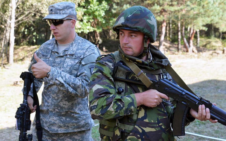 Sgt. Kevin Crosby of the 173rd Airborne Brigade gives a thumbs up after showing Romanian soldiers cordon-and-search tactics at Exercise Rapid Trident near Yavoriv, Ukraine, Thursday, Sept. 18, 2014.