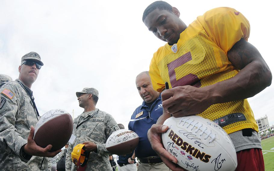 Fort Lee's Spc. Ruben Vazquez waits as Washington Redskins quarterback hopeful Pat White signs footballs during a special visit by soldiers to the team's training camp in Richmond, Va., Aug. 14, 2013.