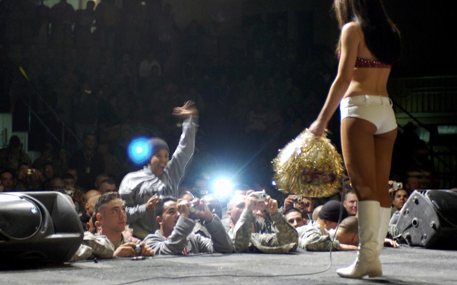 Washington Redskins cheerleader, Abby, invites U.S. troops up to the stage for the next performance during a show for Morale Welfare and Recreation on Contingency Operating Base Speicher, Tikrit, Iraq, on November 24, 2007. The cheerleaders visited during a tour of Iraq to show support for the troops.