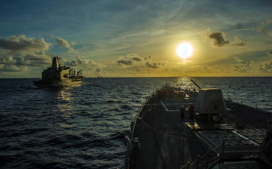 The Arleigh Burke-class guided-missile destroyer USS Mustin maneuvers alongside the Lewis and Clark-class dry cargo ship USNS Pecos to conduct a replenishment-at-sea during Valiant Shield 2014.