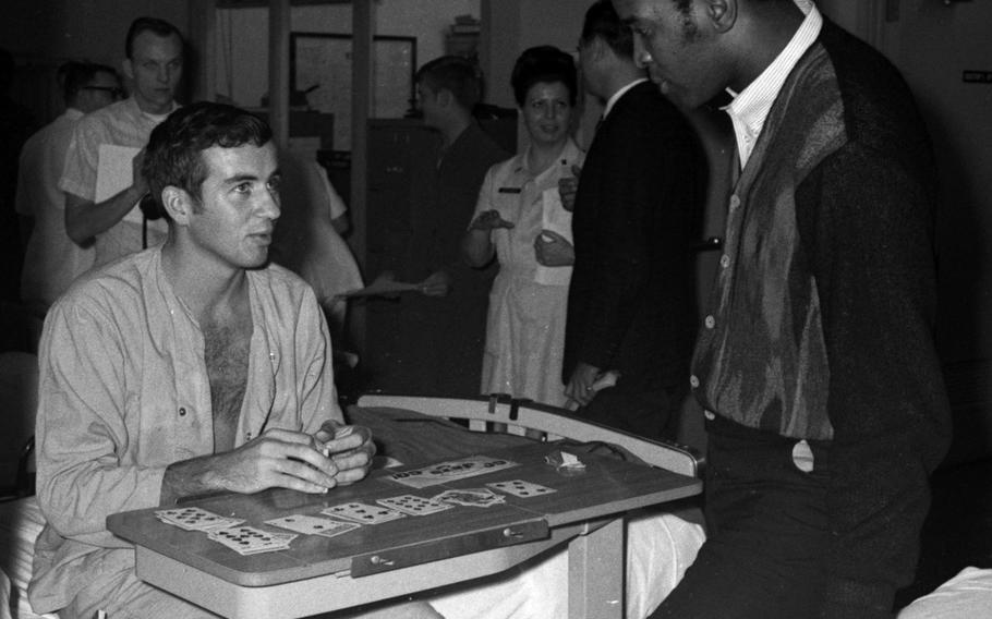 Marv Fleming of the Green Bay Packers talks with a servicemember at the U.S. Army Hospital on Camp Oji, Japan, in January, 1969.