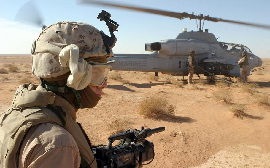 In this 2007 file photo, U.S. Marine Corps Corporal Michael L. Haas, a videographer with 2nd Marine Aircraft Wing, Forward Combat Camera, documents Marines with Marine Heavy Helicopter Squadron 361 refueling an AH-1W Super Cobra from Marine Light/Attack Helicopter Squadron 773 during an aero scout mission over the Al Anbar province, Iraq, on Dec. 8, 2007.
